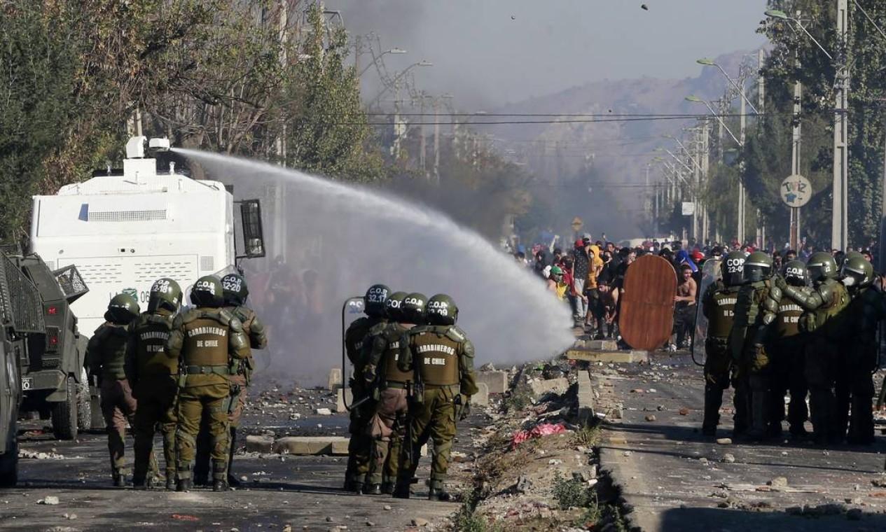 Manifestantes entram em confronto com a polícia durante protesto por falta de comida na capital chilena em meio à pandemia de Covid-19 Foto: RAMON MONROY / AFP