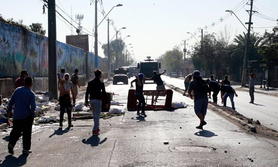 Manifestantes atiram pedras na direção das forças de segurança em Santiago. Eles reclamam da falta de comida e trabalho em meio ao bloqueio contínuo da capital chilena como resultado do coronavírus Foto: PABLO ROJAS / AFP