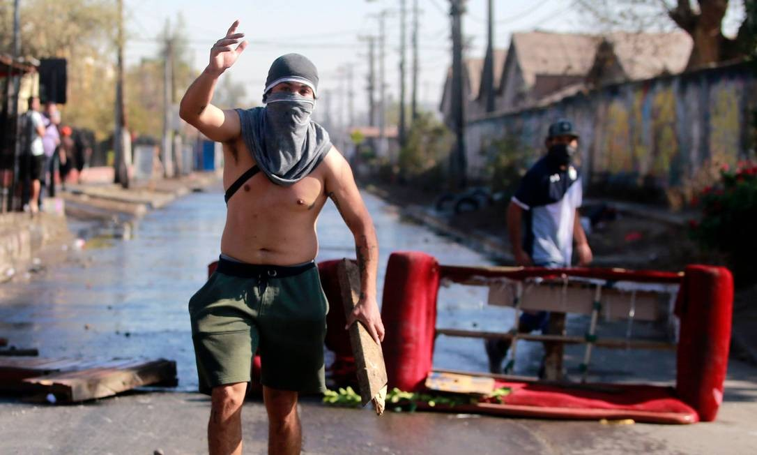 Um manifestante durante confrontos com a polícia de choque, em protesto contra o governo do presidente chileno, em Santiago Foto: RAMON MONROY / AFP
