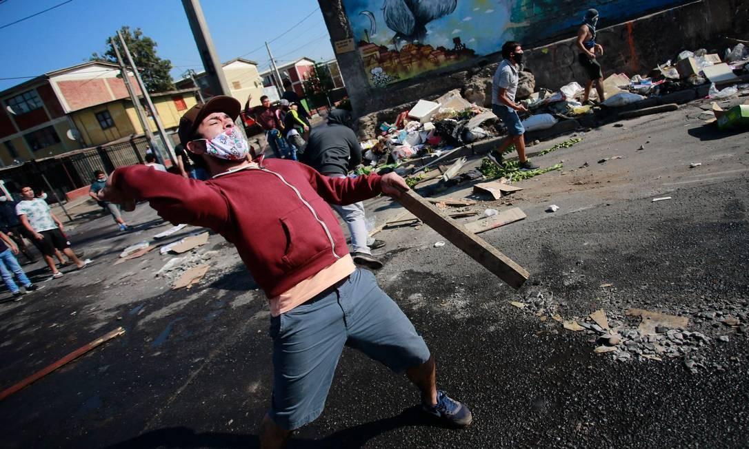 Manifestante atira objetos contra a polícia de choque durante um protesto contra o governo do presidente Sebastián Piñera Foto: PABLO ROJAS / AFP