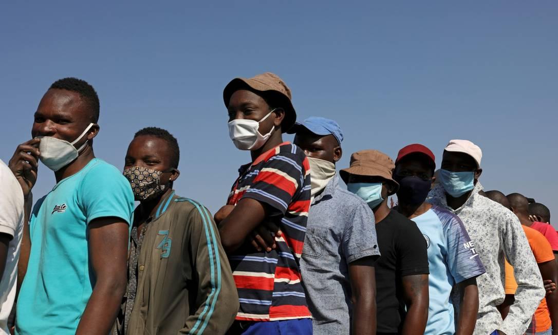 Na África do Sul, pessoas de máscara esperam para receber comida Foto: Siphiwe Sibeko / REUTERS
