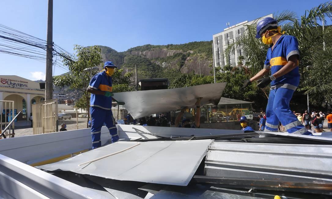 Agentes da Comlurb carregam caminhão com chapas metálicas de barracas instaladas no entorno do camelódrom da Rocinha, em São Conrado, Zona Sul do Rio Foto: Fabiano Rocha / Agência O Globo