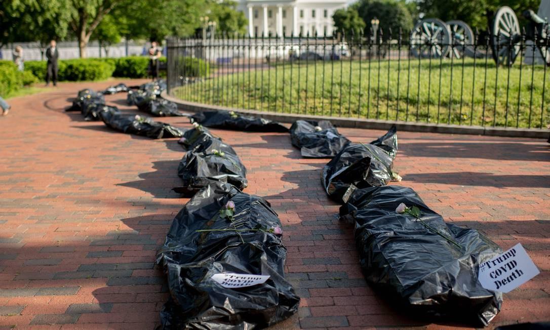 Manifestantes exibem sacos de corpos falsos durante um protesto em frente à Casa Branca, contra a resposta do governo Trump à pandemia de COVID-19 Foto: ERIC BARADAT / AFP
