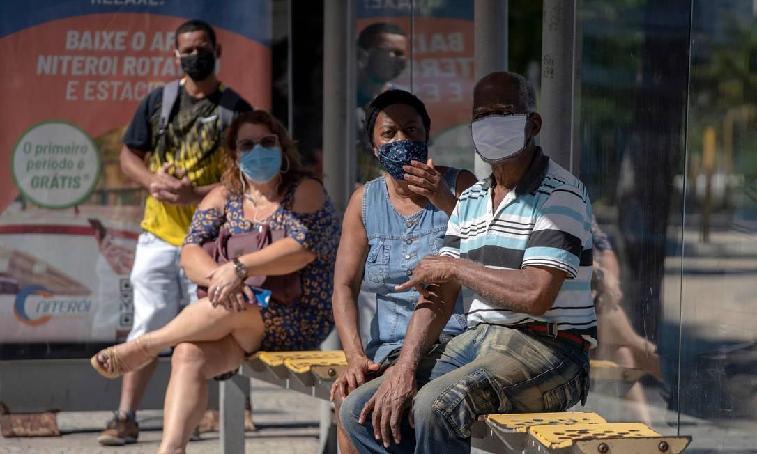 Uso obrigatório: moradores usam máscara em ponto de ônibus, em Icaraí. Quem descumprir medida pode ser multado em R$ 180 Foto: Mauro Pimentel / AFP