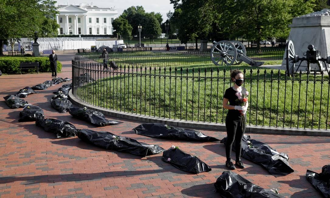 Margot Bloch fica ao lado de uma fileira de sacos representando corpos enquanto segura flores durante um ato em homenagem às vítimas da COVID-19, fora da Casa Branca, em Washington, EUA Foto: TOM BRENNER / REUTERS