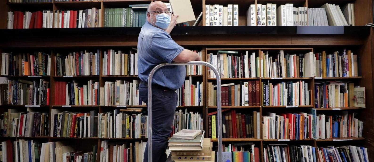 O livreiro Philippe Seyrat usa máscara protetora na livraria La Sorbonne, em Nice, na França, onde o comércio começa a reabrir aos poucos Foto: ERIC GAILLARD / REUTERS