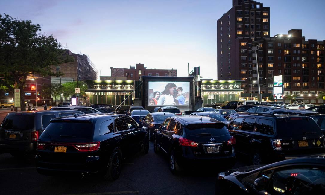 Pessoas assistem filmes dentro de seus carros em cinema drive-in no Queens, Nova York Foto: JOHANNES EISELE / AFP