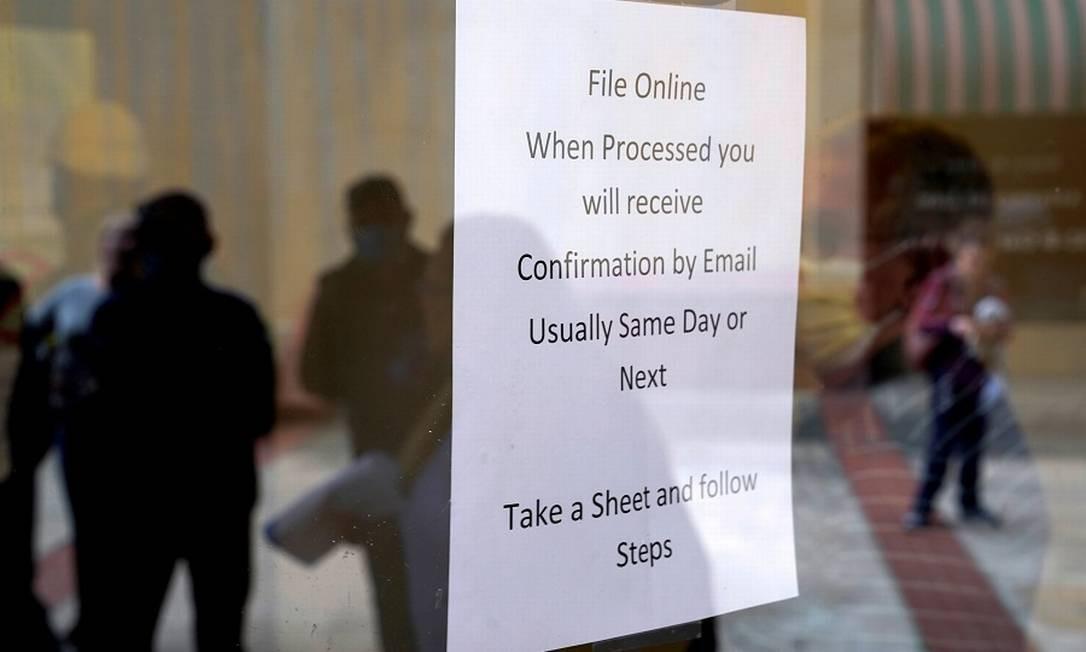 Aviso e fila para seguro desemprego em Fort Smith, estado americano do Arkansas. Foto: Nick Oxford / REUTERS