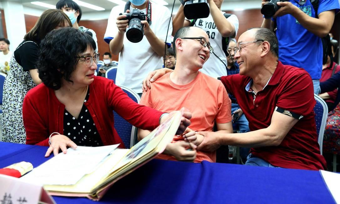 Depois de localizado, Mao Yin, de 34 anos, que sorri entre seus pais biológicos, foi submetido a teste de DNA que comprovou o laço parental apontado pelo sistema de reconhecimento facial Foto: STR / AFP