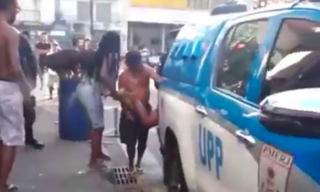 Em vídeo compartilhado por moradores, é possível ver momento em que policiais colocam homem baleado dentro da viatura em meio a protestos Foto: Reprodução
