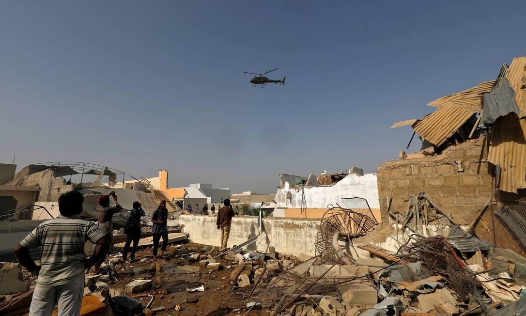 Helicóptero sobrevoa o local de um acidente de avião em uma área residencial perto de um aeroporto em Karachi, Paquistão Foto: AKHTAR SOOMRO / REUTERS