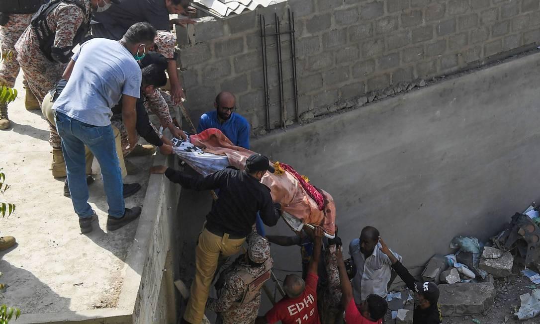 Equipes de resgate deslocam um corpo do local onde caiu a aeronave da Pakistan International Airlines, numa área residencial em Karachi, nesta sexta-feira Foto: ASIF HASSAN / AFP