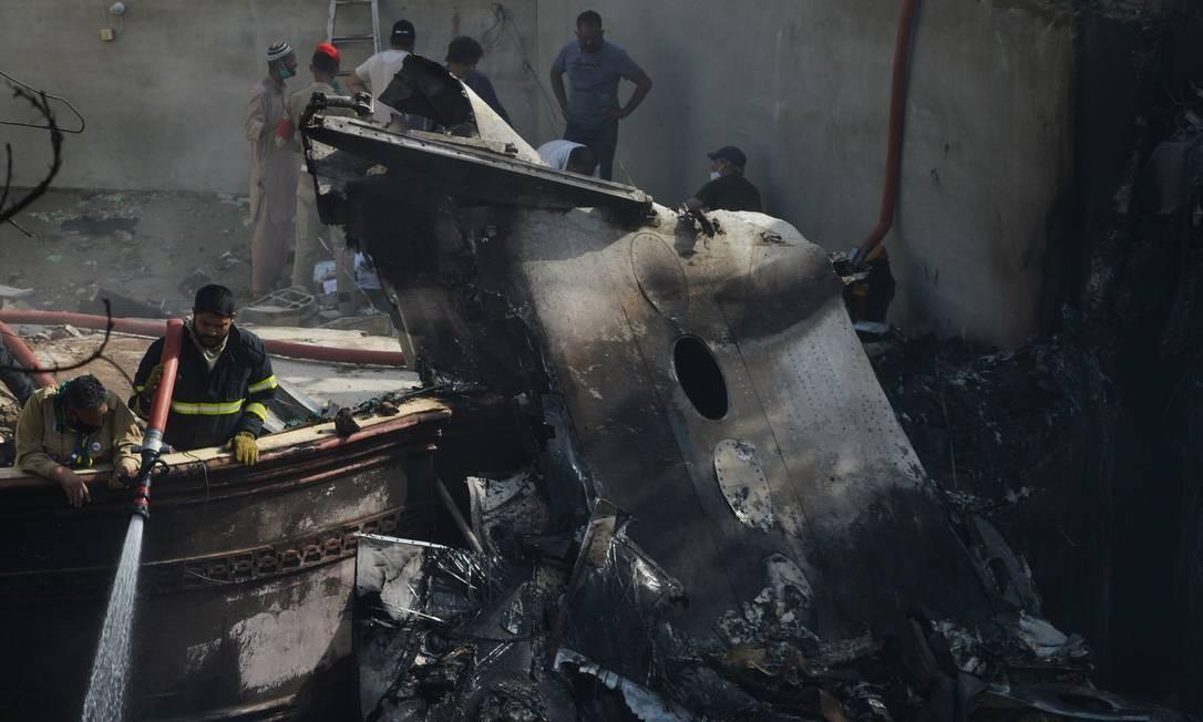 Bombeiro pulveriza água sobre os destroços da aeronave da Pakistan International Airlines que caiu na manhã desta sexta-feira, em Karachi, no Paquistão Foto: RIZWAN TABASSUM / AFP