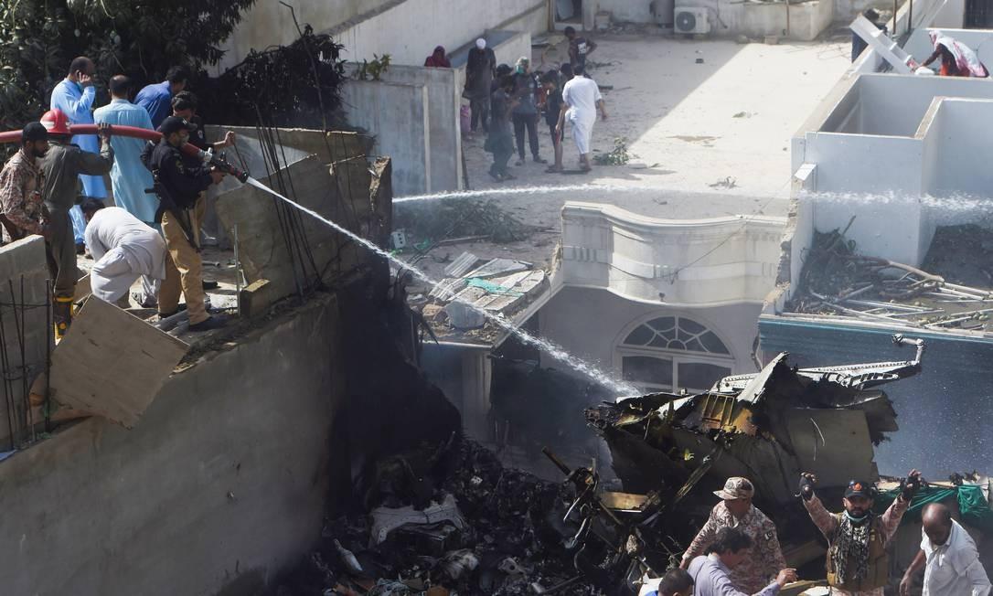 Polícia paquistanesa dá apoio ao trabalho dos bombeiros de combater focos remanescentes de incêndio Foto: ASIF HASSAN / AFP