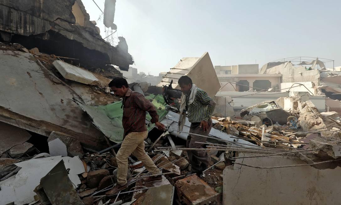 Homens andam sobre destroços no local de um acidente de avião de passageiros em uma área residencial perto de um aeroporto em Karachi, Paquistão Foto: AKHTAR SOOMRO / REUTERS