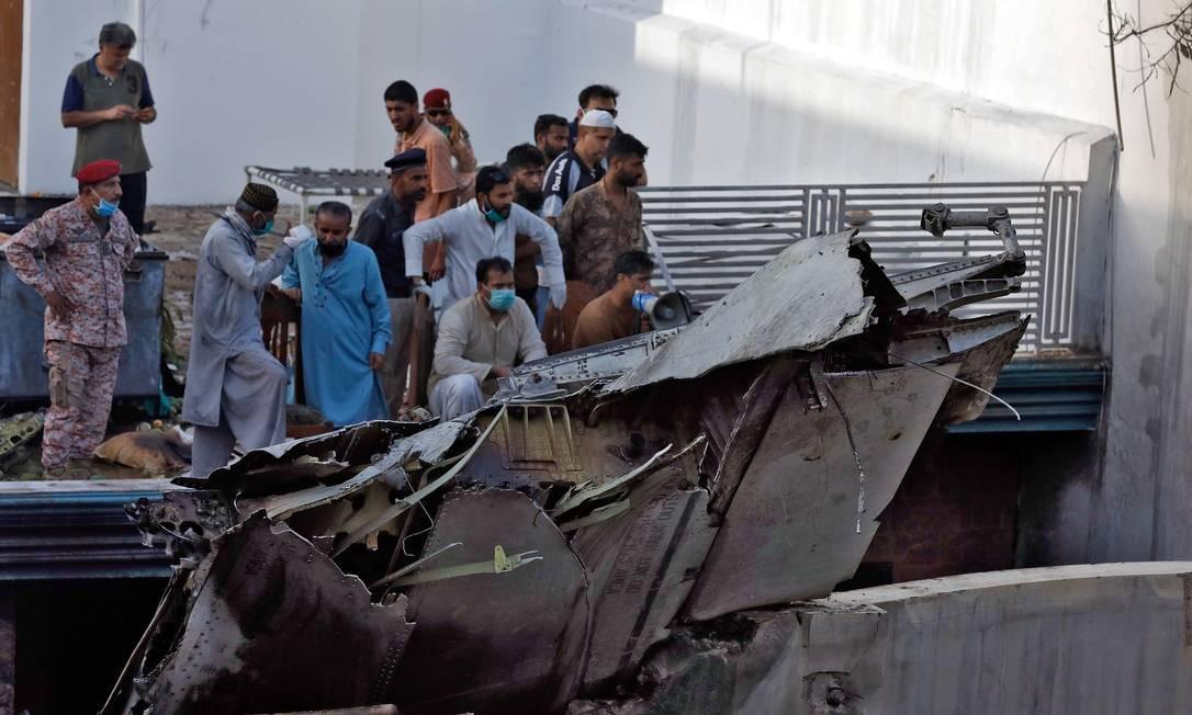 Tragédia atraiu multidão de curiosos e também de voluntários para auxiliar nas buscas Foto: AKHTAR SOOMRO / REUTERS