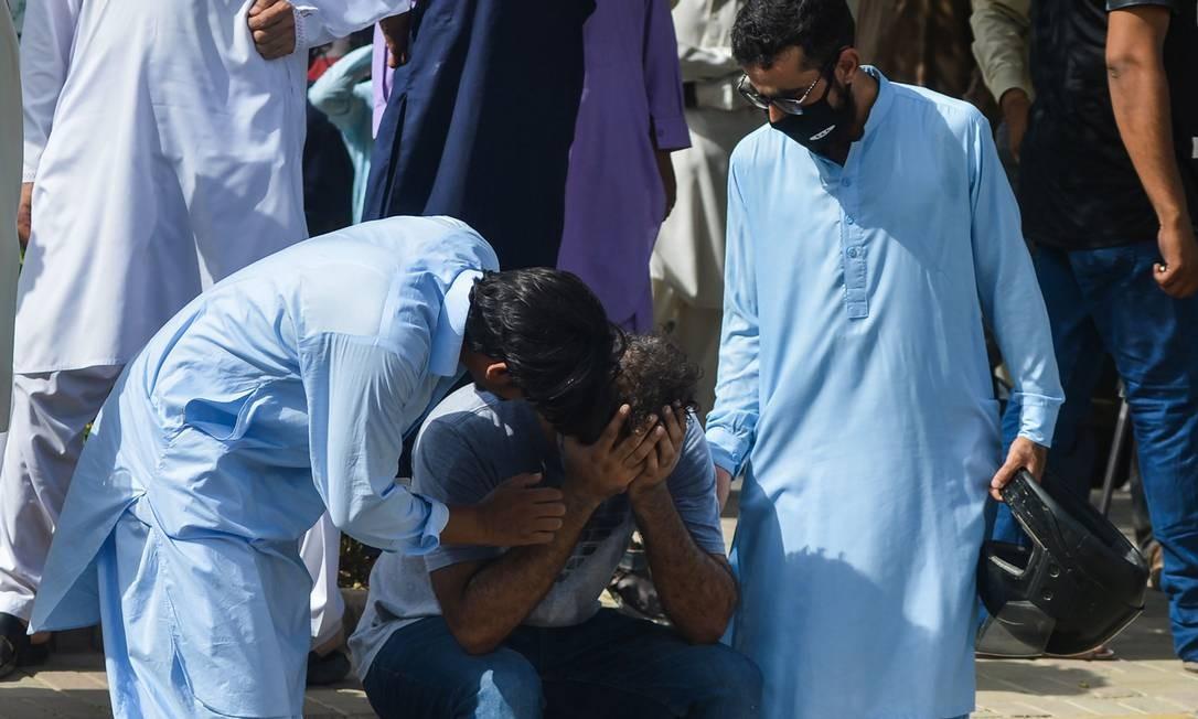Pessoas confortam parente de uma vítima da queda do avião em Karachi Foto: RIZWAN TABASSUM / AFP
