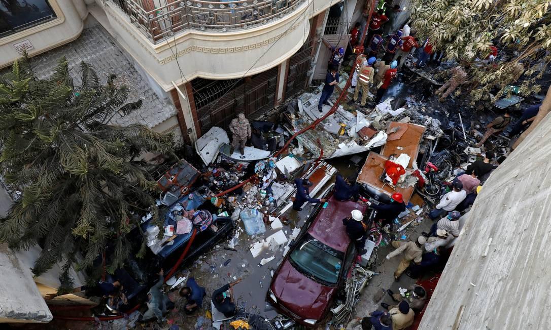 Equipes de resgate se reúnem no local do acidente de avião em uma área residencial, em Karachi Foto: AKHTAR SOOMRO / REUTERS
