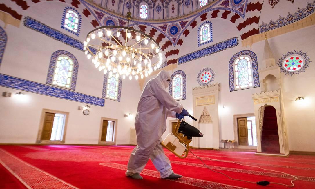 Trabalhador pulveriza desinfetante dentro da mesquita Banya Bashi, em Sofia, capital da Bulgária, contra o novo coronavírus, antes da última oração de sexta-feira do mês de jejum do Ramadã Foto: NIKOLAY DOYCHINOV / AFP