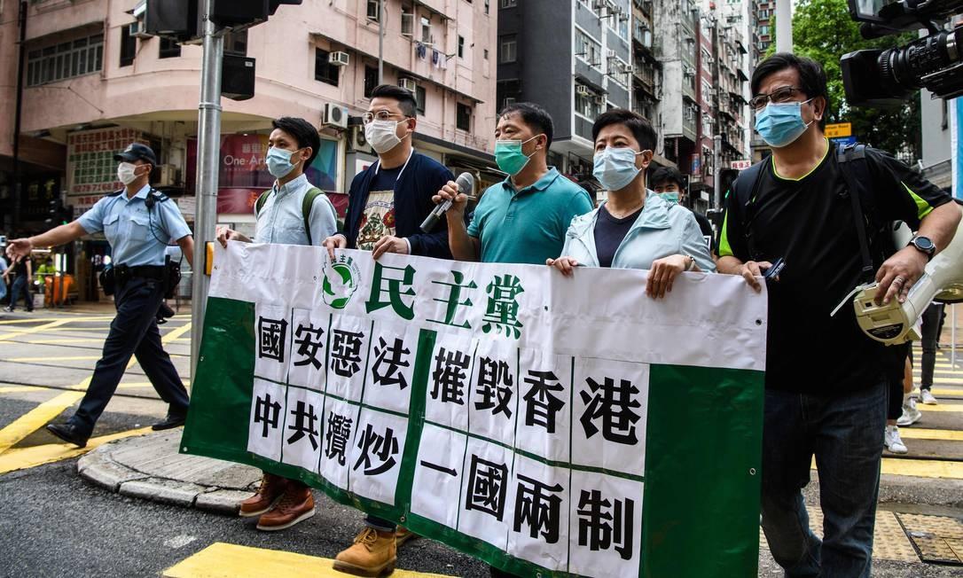 """Manifestantes pró-democracia seguram uma faixa que se diz: """"lei viciosa de segurança nacional destrói Hong Kong; comunistas chineses buscam a destruição mútua de dois sistemas de um país"""" Foto: ANTHONY WALLACE / AFP"""