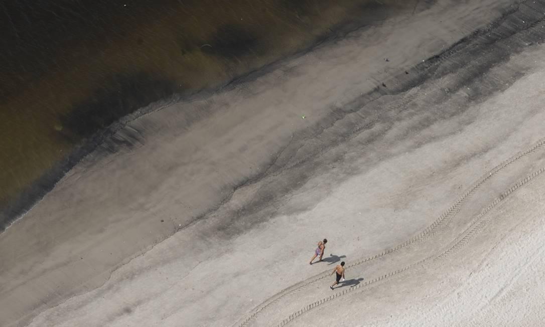 Pessoas correm próximo à beiramar onde, além da água turva, vê-se areia poluída Foto: Márcia Foletto / Agência O Globo