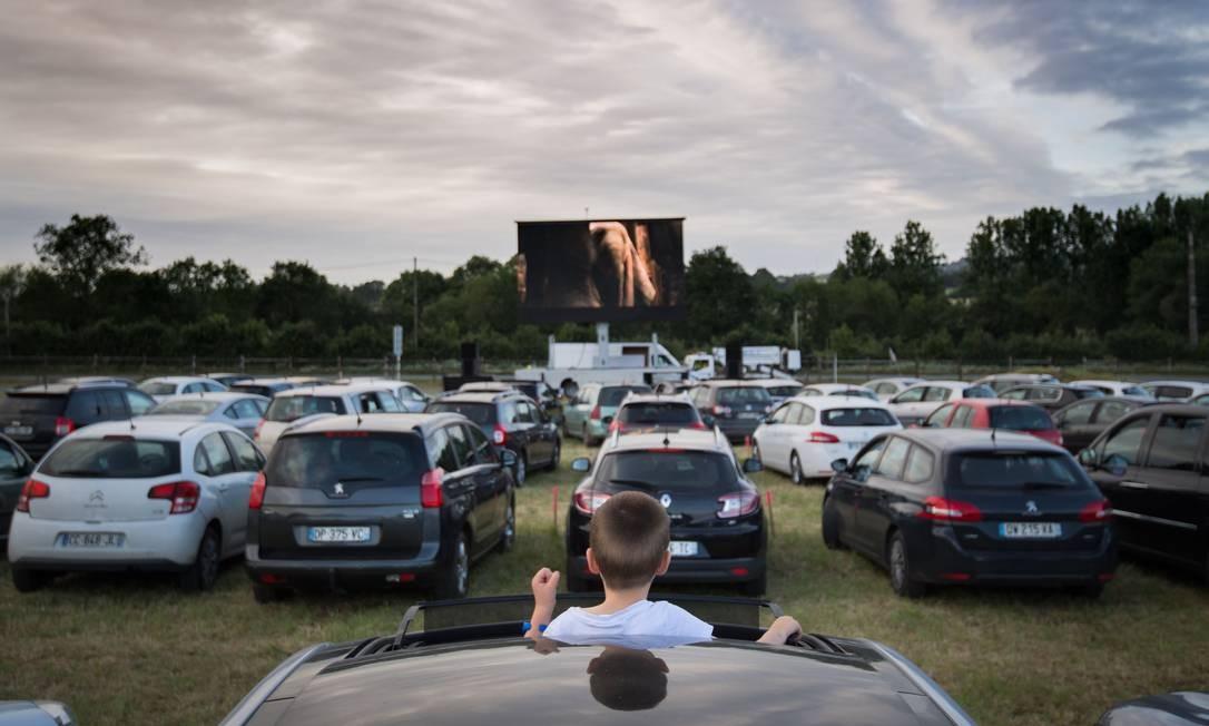 Garoto de pé no teto solar assiste a um filmeem um cinema drive-in, em Les Herbiers, oeste da França, enquanto a França facilita as medidas de bloqueio tomadas para conter a propagação do novo coronavírus Foto: LOIC VENANCE / AFP