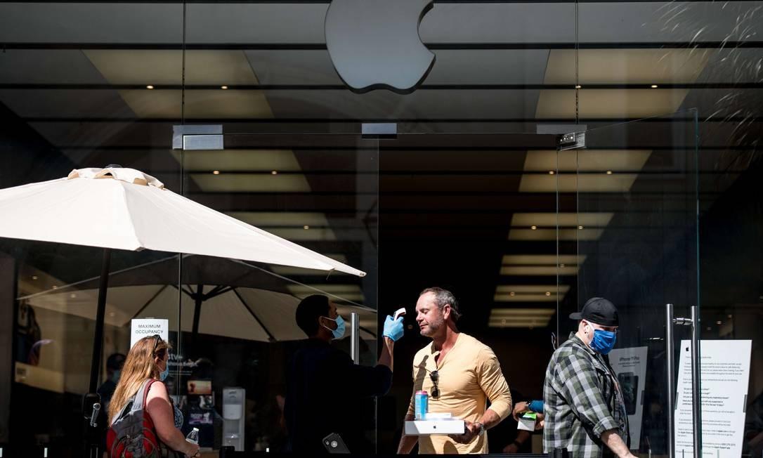 Demanda em alta. Segurança mede temperatura de cliente na porta de uma loja da Apple em Charleston, nos EUA Foto: Sean Rayford / AFP