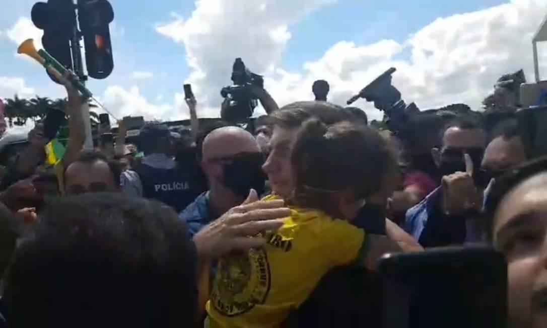 Sem mácara, Bolsonaro segura criança no colo, durante manifestação de simpatizantes do governo, em Brasília Foto: Reprodução