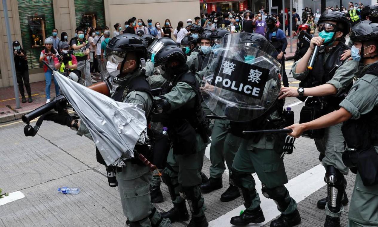 Um guarda-chuva é jogado contra a polícia durante a manifestanção. Ato na cidade é o maior desde o início da epidemia do novo coronavírus Foto: TYRONE SIU / REUTERS