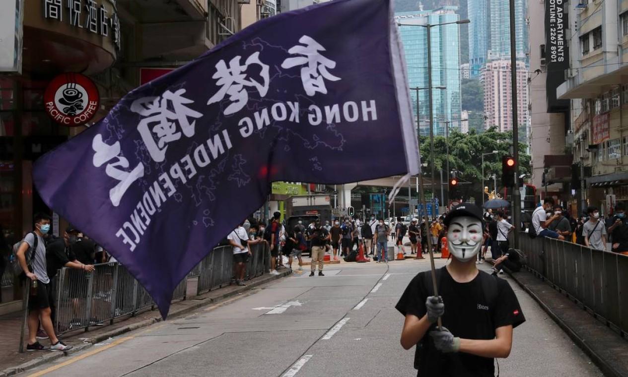 Um manifestante antigoverno mascarado segura uma bandeira que apoia a independência de Hong Kong durante protesto neste domingo Foto: TYRONE SIU / REUTERS