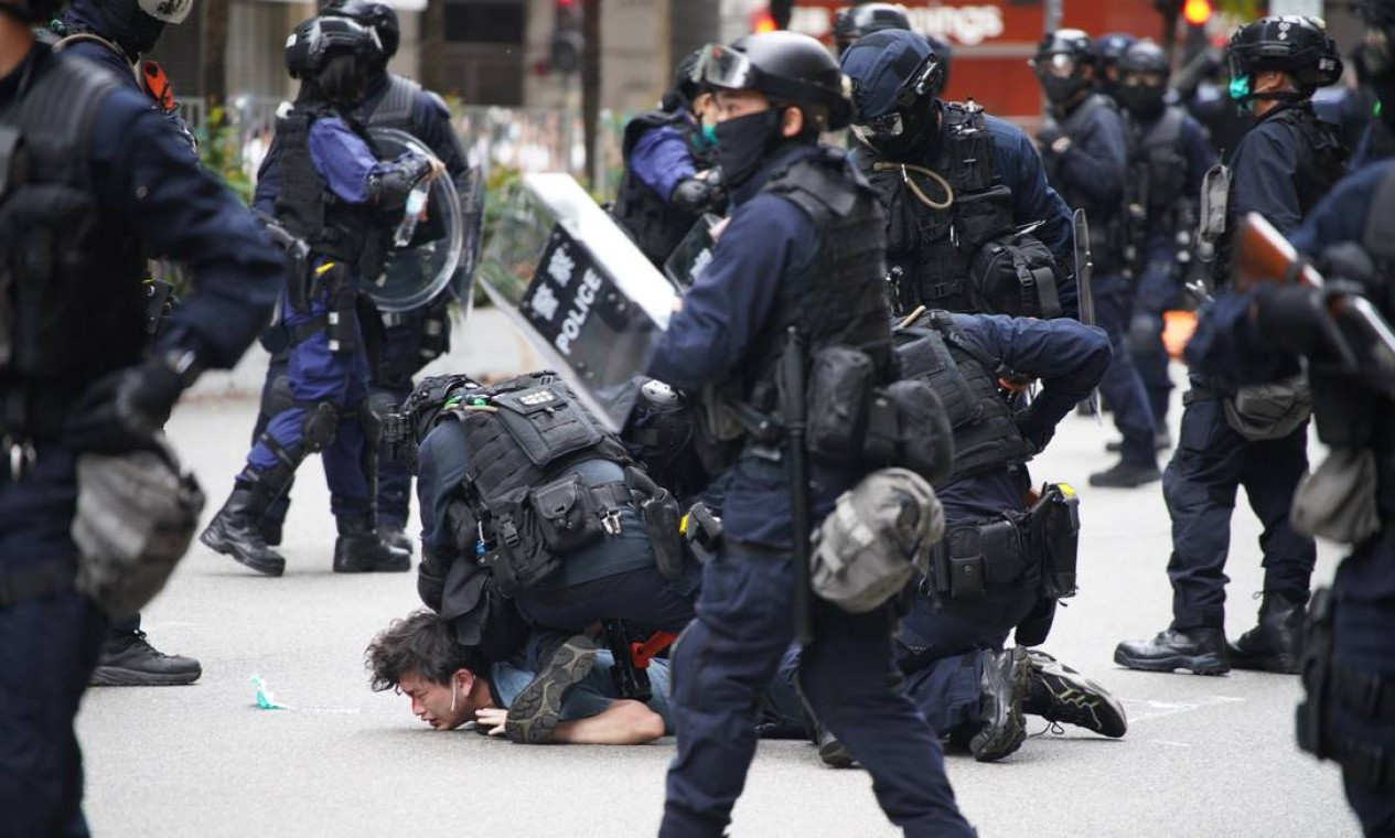 Policiais detêm um manifestante em Wanchai, Hong Kong, neste domingo, quando milhares de manifestantes saíram às ruas para protestar contra proposta de lei de segurança nacional Foto: YAN ZHAO / AFP