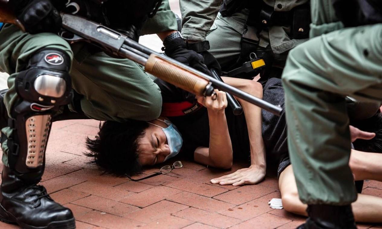Manifestantes é detido pela polícia no distrito de Causeway Bay, em Hong Kong, durante protesto neste domingo Foto: ISAAC LAWRENCE / AFP