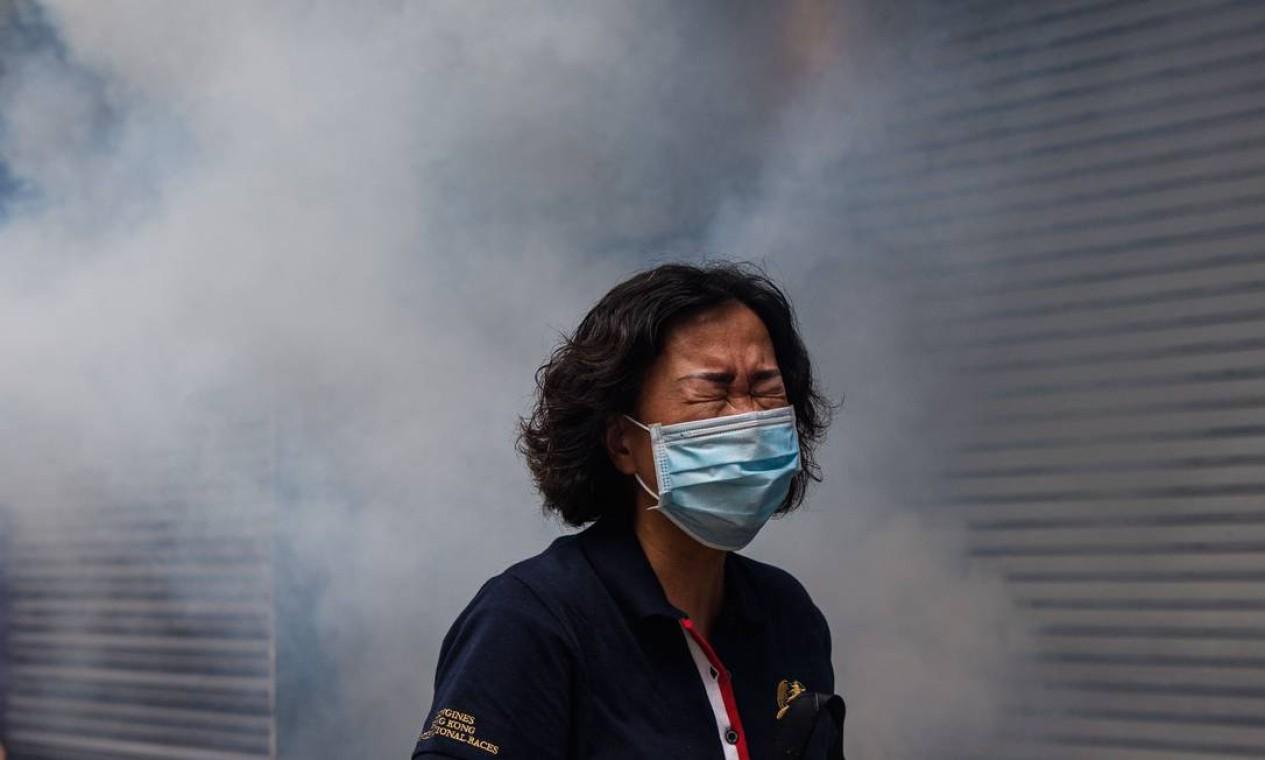 Uma mulher é vista em meio à fumaça de gás lacrimogêneo disparada pela polícias para dispersar os manifestantes Foto: ANTHONY WALLACE / AFP