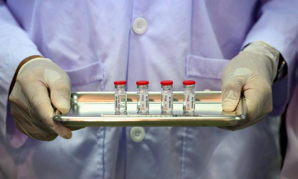 Técnico de laboratório segura uma bandeja com doses da vacina em desenvolvimento contra o coronavírus pronto para testes em macacos, na Tailândia Foto: MLADEN ANTONOV / AFP - 23/03/2020