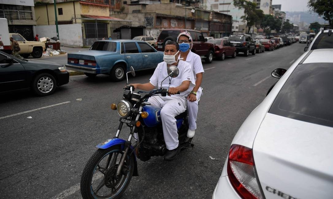 Profissionais da saúde aguardam em fila para abastecer motocicleta em posto de gasolina em Caracas Foto: FEDERICO PARRA / AFP