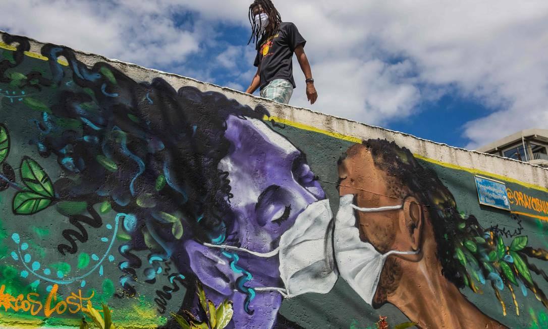 Um homem usando uma máscara facial passa por um grafite do artista Marcos Costa na entrada da favela Solar de Unhao, em Salvador. Foto: ANTONELLO VENERI / AFP
