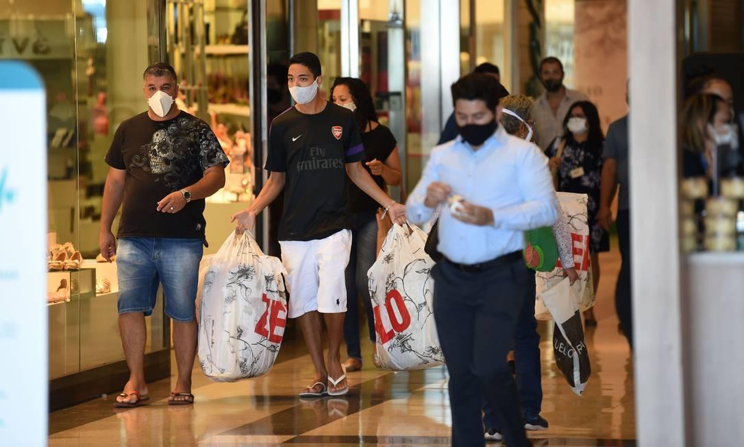 As pessoas usam máscara em um shopping em Brasília, no primeiro dia de reabertura de negócios na cidade em meio à pandemia de coronavírus Foto: EVARISTO SA / AFP