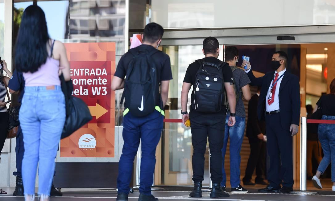 As pessoas esperam na fila para verificar a temperatura corporal antes de entrar em um shopping em Brasília Foto: EVARISTO SA / AFP