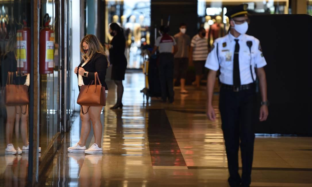 Uso de máscara nos estabelecimentos comerciais segue sendo obrigatório. Além disso, estacionamentos devem ser limitados à metade da capacidade, e uso de provadores nas lojas está proibido Foto: EVARISTO SA / AFP