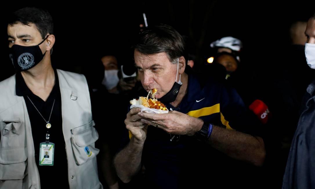 O presidente Jair Bolsonaro come um cachorro-quente em uma lanchonete de rua, em meio ao surto de coronavírus, em Brasília, gerando aglomeração com sua presença Foto: ADRIANO MACHADO / REUTERS
