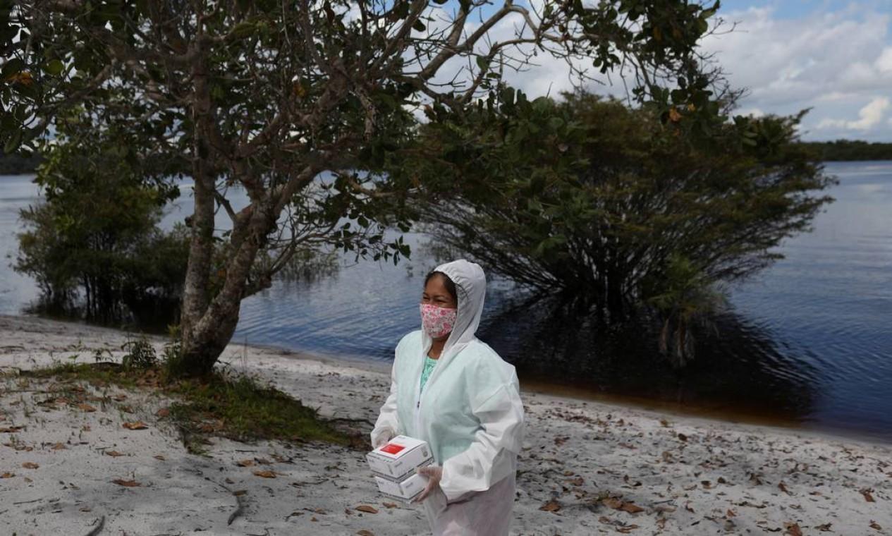 A técnica de enfermagem indígena Kambeba, Neurilene Cruz, 36 anos, realiza testes para COVID-19 às margens do rio Negro, na aldeia Tres Unidos, estado da Amazônia Foto: BRUNO KELLY / REUTERS