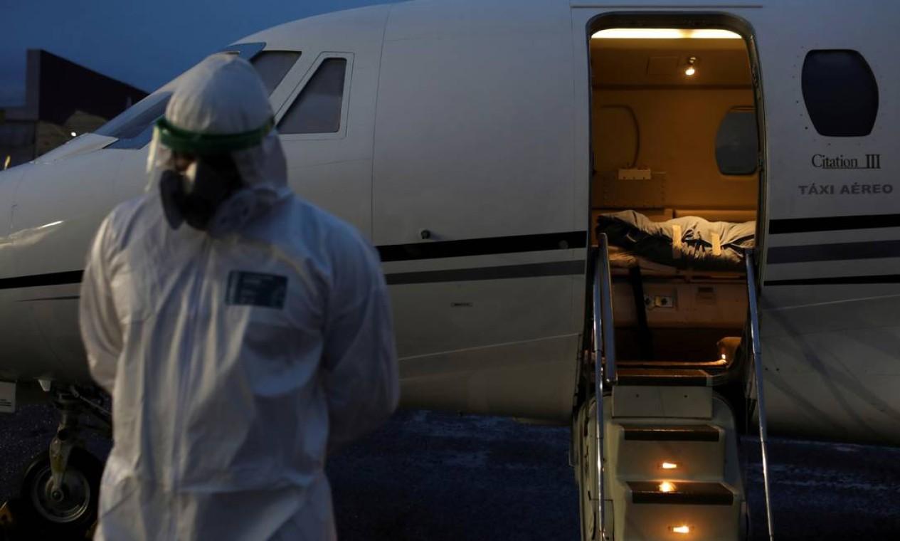 Um profissional de saúde em roupas de proteção é visto em frente ao corpo de Laureano Ferraz, 78, indígena Wanano, que faleceu devido à COVID-19, depois de chegar de jato na UTI de São Gabriel da Cachoeira para Manaus Foto: BRUNO KELLY / REUTERS