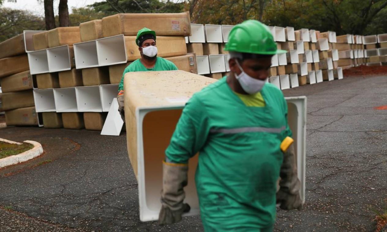 Homens carregam caixas a serem instaladas para os caixões no cemitério municipal de São Pedro, em São Paulo Foto: AMANDA PEROBELLI / REUTERS