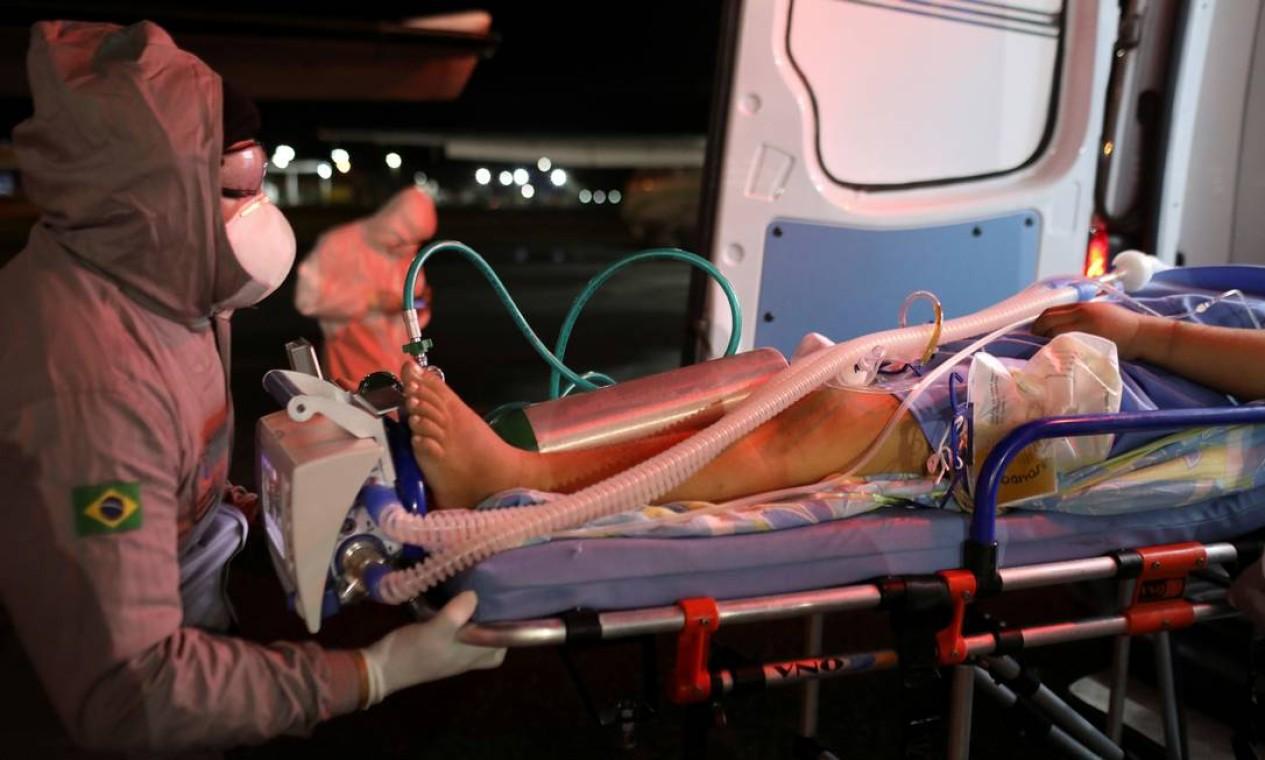 Mulher grávida com COVID-19 é levada de ambulância por um profissional de saúde depois de chegar de Coari a Manaus em um jato de UTI Foto: BRUNO KELLY / REUTERS