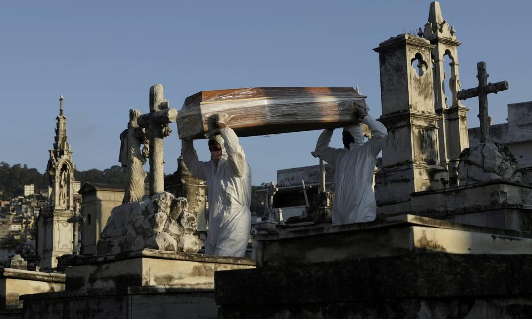 Coveiros carregam o caixão uma vítima da Covid-19 durante seu funeral, no Rio de Janeiro Foto: Ricardo Soares / Reuters