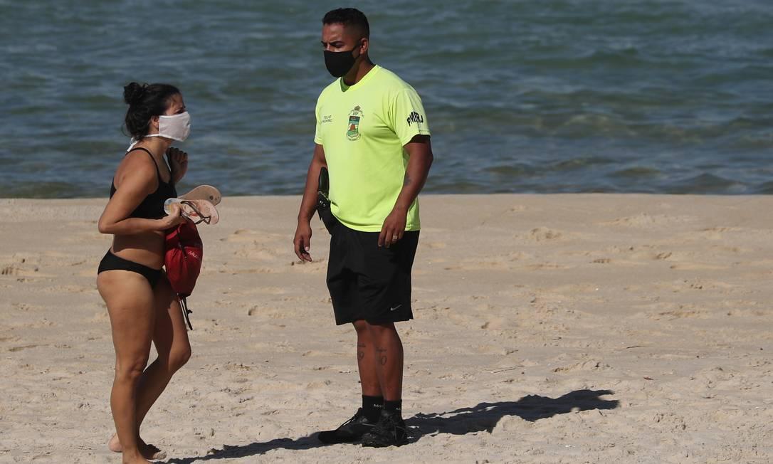 Um policial ordena que um banhista abandone a Praia de São Conrado após o fechamento das praias, em meio ao surto de coronavírus, no Rio de Janeiro Foto: SERGIO MORAES / REUTERS