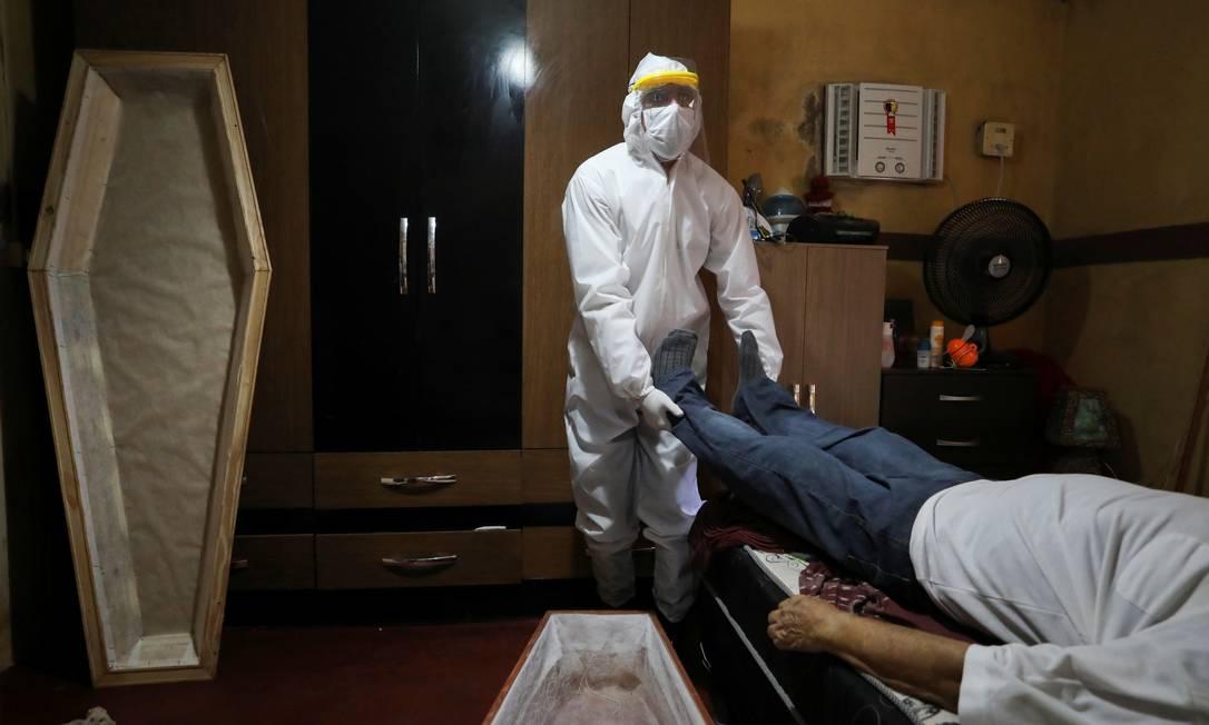 Funcionário de um serviço funerário se prepara para remover o corpo de um homem que morreu em casa em meio ao surto de COVID-19, no bairro de Tancredo Neves, em Manaus Foto: Bruno Kelly / Reuters - 07/05/2020