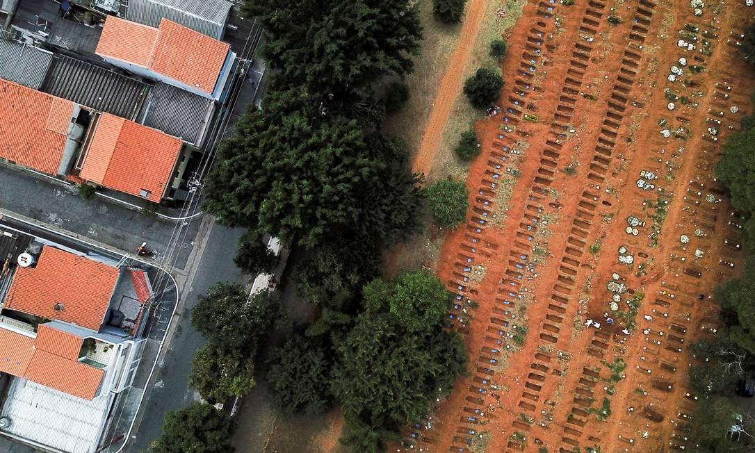 Coveiros enterram um caixão próximo a sepulturas abertas enquanto a disseminação do novo coronavírus continua fazendo vítimas, no cemitério de Vila Formosa, em São Paulo Foto: AMANDA PEROBELLI / REUTERS