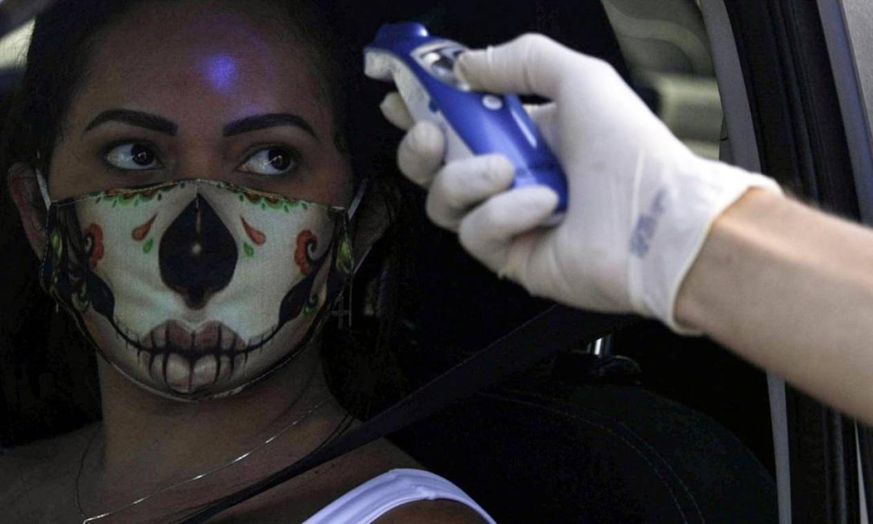 Um agente verifica a temperatura de um motorista na entrada da cidade de Niterói durante seu primeiro dia de bloqueio total, perto do Rio de Janeiro Foto: RICARDO MORAES / Reuters