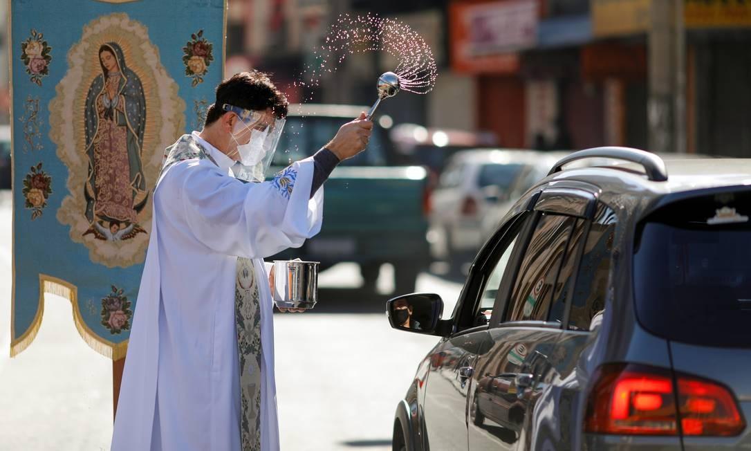 O padre Reginaldo Manzotti borrifa água benta nos motoristas no sistema drive-thru de bênçãos durante o Dia das Mães, em Curitiba Foto: RODOLFO BUHRER / REUTERS